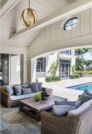 beautiful indoor outdoor living room design with clic wicker furniture blue accent pillows and a modern br chandelier