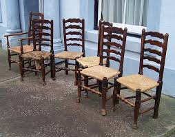 an early 19th century matched set of six oak ladderback dining chairs with rush seats one requiring renewing and front legs with circular tap tops