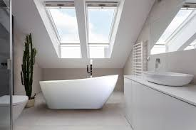 freestanding tub in white bathroom with sky light
