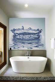 minimalis bathroom decor white bathtub big blue water painting hanged white towel stone area big mirror white ceiling