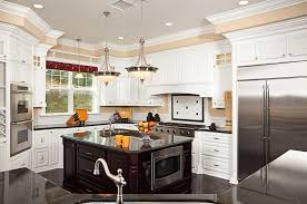 custom country kitchen with white cabinets black countertops tile backsplash and island with sink