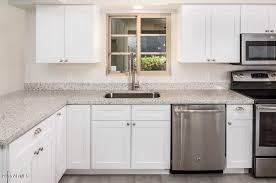 white shaker cabinets with quartz countertops. this kitchen remodel features j\u0026k white shaker cabinets with peppercorn quartz countertops. the stainless steel appliances are perfect accent to countertops c