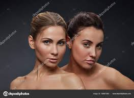 two women natural makeup dark background stock photo