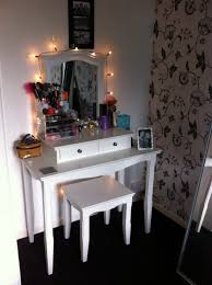 small and narrow corner wood makeup desk design painted with white color plus double drawer under makeup storage and lighted mirror plus chair without back