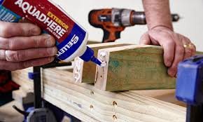 applying glue on the end of timber rail