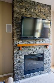 fascinating stacked stone fireplace featuring wall mounted flat tv