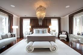 stunning chandelier sits at the center of the expansive contemporary bedroom