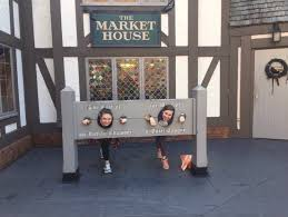 two female students with their heads inside colonial style stocks at busch gardens the stocks