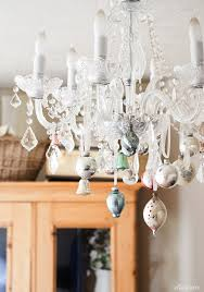 i love this idea of putting vintage ornaments on a chandelier