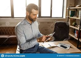 Use Tablet As Phone Young Handsome Businessman Sit On Table And Use Tablet In