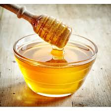 a dish of honey with a wooden dipper