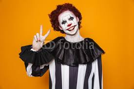 scary clown man 20s wearing black costume and makeup looking at camera isolated over