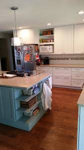 remodeled kitchen has white shaker cabinets with open shelves above  microwave cabinet, custom glass backsplash