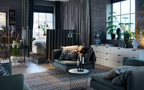 Dark grey open plan studio with a bed in the corner surrounded by room  dividers.