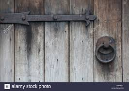 old wrought iron hinges and door handle on weathered wooden door stock image