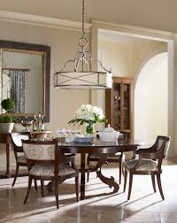 comfortable dining table for ten users with bright drum shade giant chandelier room accompanied flower and the mirror