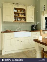 white belfast sink in cream fitted unit below wallcupboard traditional country kitchen painted farrowball paint kitchens b97 cream