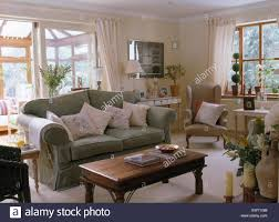 sage green sofa. Beautiful Sofa Pale Cushions On Sage Green Sofa Beside Indonesian Wood Table In Country  Sitting Room With Glass For Sage Green Sofa O
