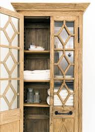 stunning bathroom features a freestanding linen cabinet restoration hardware georgian fretwork glass double door cabinet