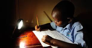 Zambian-boy-studies-using-a-solar-lantern_Patrick-Bentley-Solar-Aid |  Lighting Global