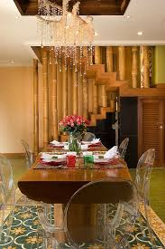 ... Staircase with bamboo railing makes up the backdrop for the eclectic  dining room [Design: