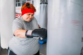 fat woman in boxing gloves works with punching bag workout in gym calories burning obese female person on hard in sport club