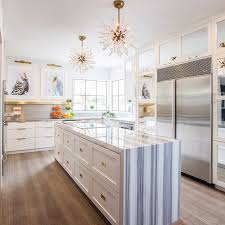 contemporary kitchen features a pair of white c light pendants arteriors diallo small chandeliers illuminating a long and narrow center island fitted