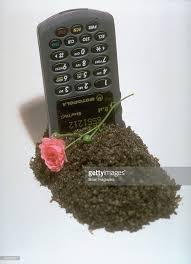 first motorola phone. motorola startac cell phone buried head-first in mound of dirt w. pink carnation first