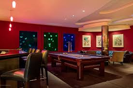 large sports themed man cave with sports jerseys on the wall and displayed throughout the space