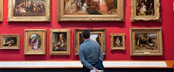 man looks at paintings in the victoria and albert museum london england uk