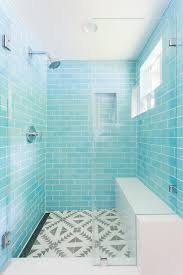 contemporary bathroom features a seamless glass shower boasting turquoise blue subway surround tiles holding a polished nickel shower kit facing a bench