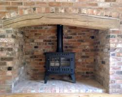 stove in large timber brick fireplace surround
