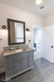 custom home builder tulsa ok bathroom with gray porcelain tile floor gray cabinets brushed nickel faucets
