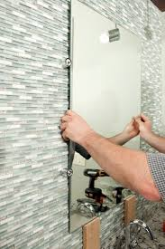 worker installing a new bathroom mirror