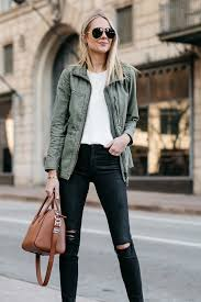 blonde woman wearing madewell fleet jacket green jacket white tank madewell black ripped skinny jeans givenchy