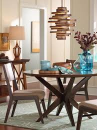 a modern chandelier hangs over a dining room table