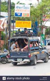 Travellers and backpackers sit in the back of pick up truck Song Tao ...