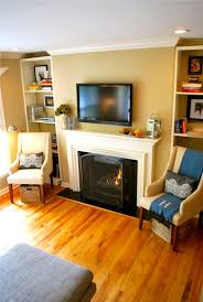 black fireplace plus white mantel combined with tv above on the cream wall on the middle