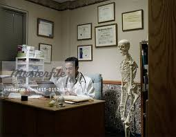 doctors office furniture. Young Male Doctor Using Laptop In Office, Skeleton Next To Desk - Stock Photo Doctors Office Furniture I