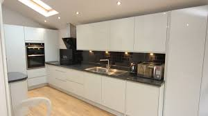glossy white doors with black granite worktops