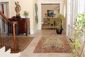 artfully paired antique persian carpets in entry hall