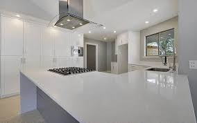 contemporary kitchen with white cabinets and arctic white quartz counters and gray island