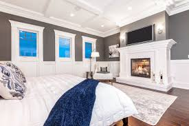 large master bedroom with white fireplace mantle and coffer ceiling