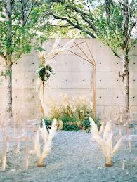 an industrial wedding ceremony arch made with copper pipes and adorned with pampas grass
