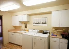 laundry room with white cabinets and ceiling lighting