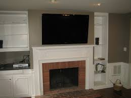 black mounted tv over brick fireplace added by white mantel and wall bookshelves and cabinet on soft grey wall