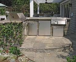 this outdoor kitchen features a tiles flooring and a bar made of bricks there s a