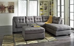 living room with grey upholstered sectional sofa with big storage ottoman coffee table with black wooden leg plus white wall shelf and picture decoration