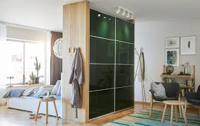 Dark green wardrobe with sliding doors used as a room divider between a  bedroom and living
