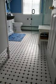 mosaic white tile bathroom floors with white door and small table facing iny blue sky